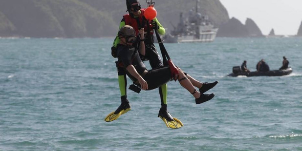 """A diver and his """"rescuer"""" are winched to safety."""