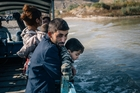 A Syrian family rides a boat across the Tigris River en route to Iraq. Photo / The Washington Post.