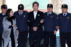 Jay Y. Lee, co-vice chairman of Samsung Group is escorted by police officers. Photo / Bloomberg