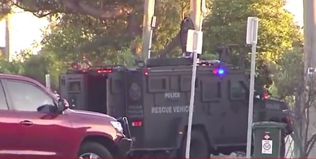 A heavily armoured vehicle rammed the front gates of the property and now police have gained access to the front yard. Photo / 7 News
