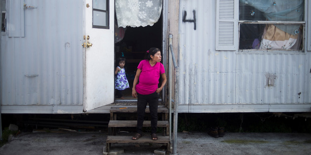 Heleodora José José watches sons Ulises and Elvis play outdoors while her daughter, Melissa, stands in the doorway. Photo / Zack Wittman for The Washington Post