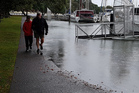 Whangarei couple Paul Mepham and Mirian Varnes stroll along a partially-flooded walkway along Riverside Dr during high tide. PHOTO/IMRAN ALI