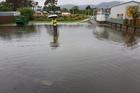 Raumati Beach School principal Mike Farrelly gumboot deep in water.