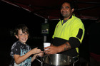 Aidan Glover, 8, receives a cup of warm pumpkin and bacon soup from Soul Soup kitchen founder Isaac Pomare.
