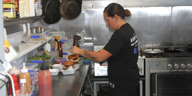 Chef Joelene Rogers putting the finishing touches to two more gourmet burgers.