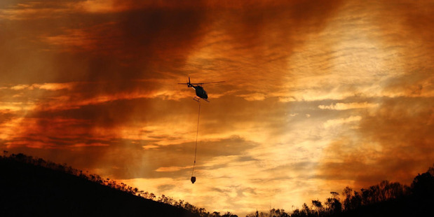Helicopters worked into the evening on Thursday to try and contain a bush fire. Photo /   Supplied