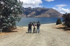 Missing skydiver Tyler Nii's parents, Bob and Nancy, and his brother, Kevin, during a blessing at Lake Wakatipu this week. Photo / Supplied