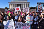 Demonstrators hold signs while cheering during the second Women's March on Washington at the Lincoln Memorial. Photo / Bill O'Leary