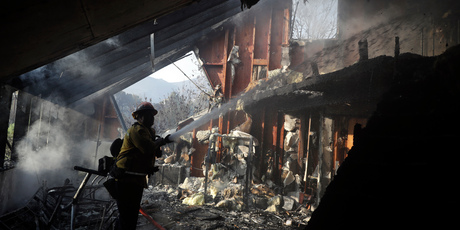 Firemen throw hot spots at a sword house that raged in Malibu. Photo / AP