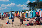 A hot and busy day beside the bathing boxes on the Dendy Street Beach in Melbourne. Photo / Getty Images.