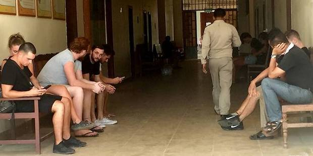 Loading The tourists arrested on indecency charges in Cambodia wait at the courthouse. Photo / Cambodia Expats Online