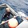Reporter James Ihaka, in the lidless shark cage, talks to skipper Boyd McGregor. Photo / Richard Robinson