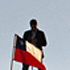 A man stands next to part of a row of 33 flags, 32 Chilean and one Bolivian, not seen, representing and honoring the 33 miners trapped at the San Jose collapsed mine in Copiapo, Chile. Photo / AP