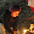 Andrea Aravena, relative of one of 33 trapped miners, lights candles next to Chilean flags outside the San Jose collapsed mine in Copiapo, Chile. Photo / AP