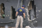 FBI agents investigate near the damaged rear wall of the Pulse Nightclub where Omar Mateen allegedly killed 49 people. Photo / Getty Images
