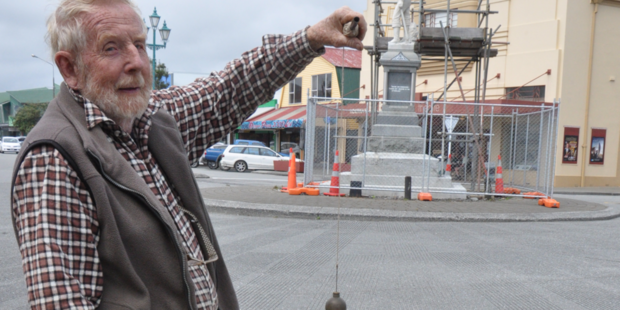 Max Dowell lines up a plumb-bob to check the level of Hokitika's pioneer statue, which he believes is slumping slightly to the south-east. Photo / Janna Sherman