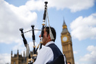 A Scottish piper plays for tourists in front of the Houses of Parliament in central London. Photo / Getty Images