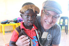 John Elliott with a child from a school in South Africa who has benefited from the buy-one-give-one policy of his company, TOMS. Elliot was the keynote speaker at PwC Herald Talks on November 16. Supp