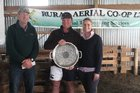 Simon and Elle Joblin in their Greenhill Station woolshed hold the trophy recognising them as winners of the 2018 Tararua Sheep and Beef Farm Business of the Year, presented by Stuart Cowan, a director of chief sponsor Rural Aerial Co-op Ltd.