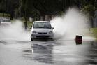 Drivers negotiate surface flooding on Portland Road, Remuera, yesterday after heavy rain. Photo / Brett Phibbs