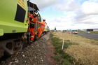 Workers release ballast from the first work train to return to the Wairoa-Napier line.  Photo / Duncan Brown