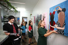 Watched by tutor Jessie Rose Foote and other students, Ella Martin, 11, from Matarau, hangs her acrylic painting called Friendship ready for the Inspire Art School exhibition. Photo / John Stone