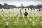 Family members walk through the field of remembrance looking for the names on crosses of those who died in World War One at the commemoration of Armistice Day at the Auckland War memorial. Photograph / Greg Bowker