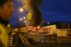 A demonstrator stands in front of a makeshift barricade set up by the yellow jackets to block the entrance of a fuel depot in Le Mans, western France. Photos / AP