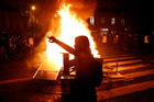 Demonstrators gather around a burning barricade during clashes with riots police, in Paris, France yesterday. Photo / AP