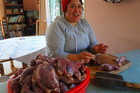 Conservation Festival organiser Stella Schmid prepares meat for mutton and possum sausages, or