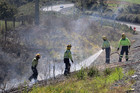 Kerikeri firefighters extinguish a blaze next to State Highway 10 at Bulls Gorge, one of several fires around Northland yesterday. Photo / Peter de Graaf