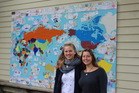 Volunteer teacher aids at Te Ra Waldorf School Sarah Alrutz and Luise Tiedt with the postcard mural they created with students. Photo / Rosalie Willis