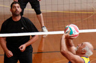 Claude Poulsen sets the ball as Aaron Manville prepares to defend at the Masters Games volleyball.